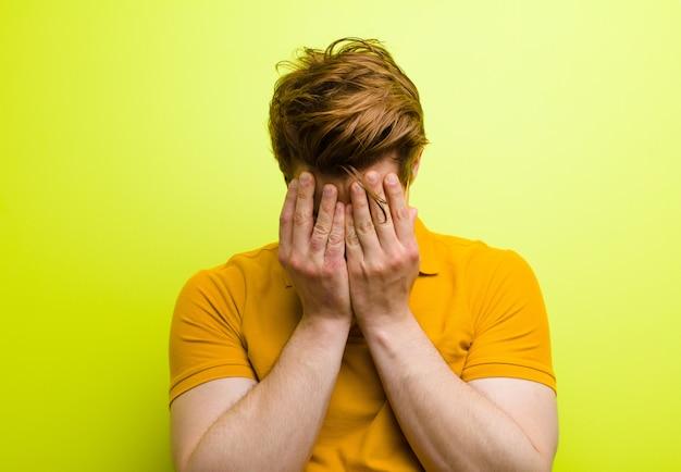 Jeune homme à tête rouge se sentant triste, frustré, nerveux et déprimé, couvrant le visage des deux mains, pleurant contre le mur de chrominance