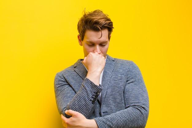 Jeune homme à la tête rouge se sentir sérieux, pensif et concerné, regardant de côté, la main appuyée contre le menton sur fond orange