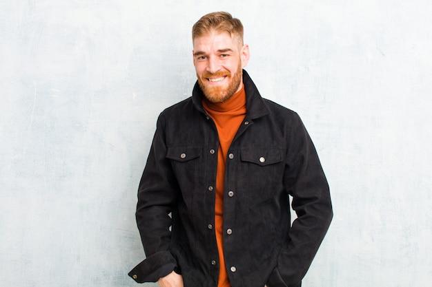 Jeune homme tête rouge souriant gaiement et nonchalamment avec une expression positive, heureuse, confiante et détendue sur le mur de grunge
