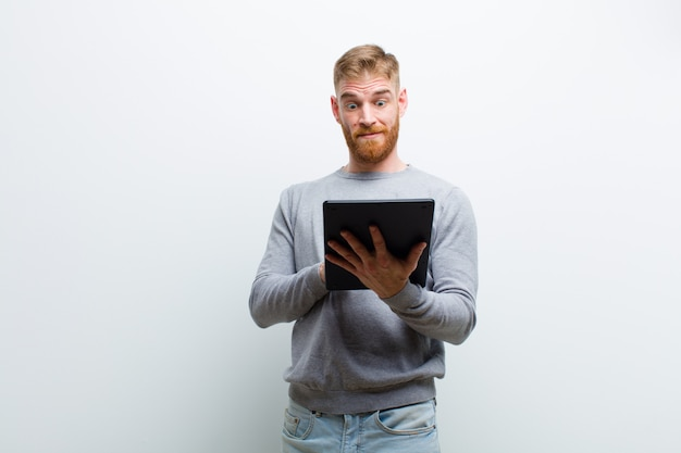 Jeune homme tête rouge tenant une tablette contre le mur blanc