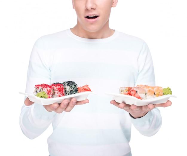 Jeune homme tient une assiette avec des sushis.