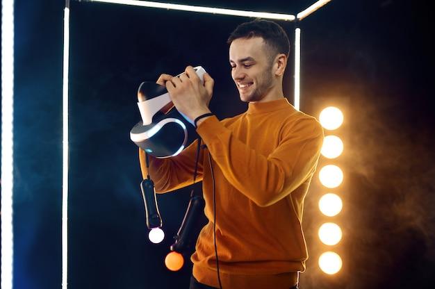 Jeune homme tient un casque de réalité virtuelle et une manette de jeu dans un cube lumineux. intérieur du club de jeu sombre, technologie vr avec vision 3d