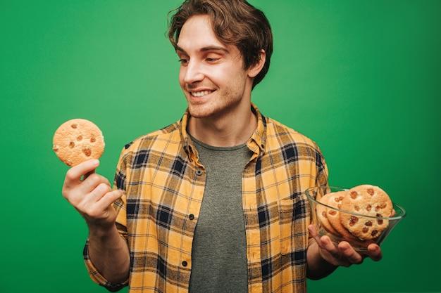 Jeune homme tient des cookies et se sent bien