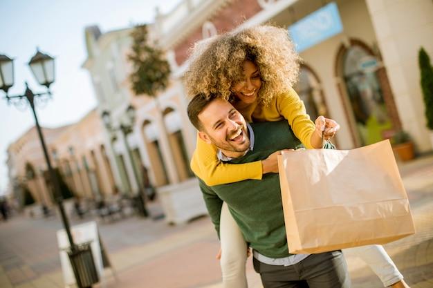 Jeune homme tient la jeune femme sur son dos, amusez-vous et faites du shopping