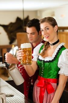 Jeune homme tirant une bière au restaurant ou au pub