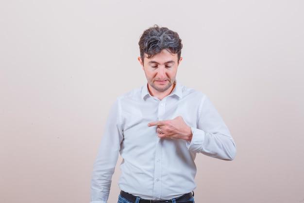 Jeune homme tirant sa chemise en chemise blanche, jeans et à la fierté