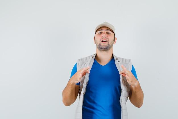 Jeune homme tirant sa veste ouverte en t-shirt, veste et à la fierté. vue de face.