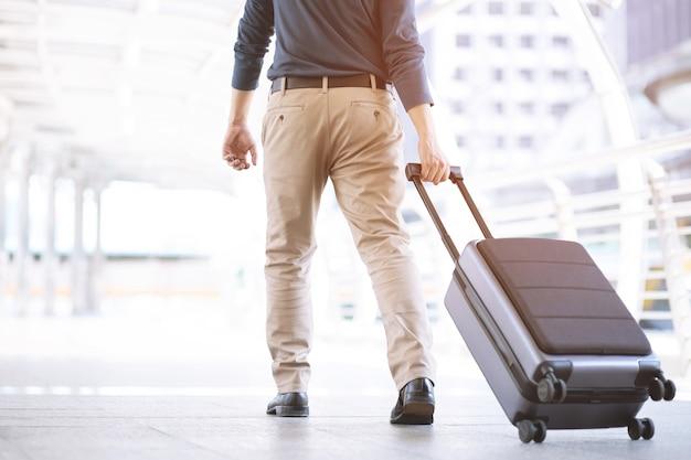 Jeune homme tirant la valise dans le terminal de l'aéroport