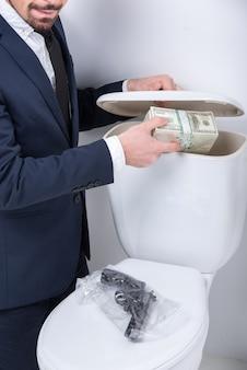 Un jeune homme tire un pistolet et de l'argent du réservoir des toilettes.