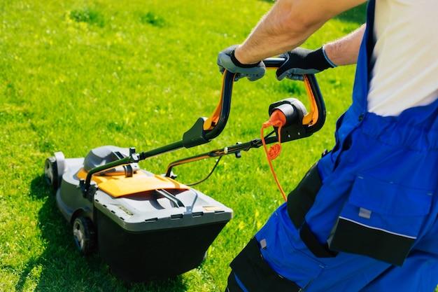Jeune homme tond la pelouse à l'aide d'une tondeuse à gazon électrique dans un costume de travailleur spécial près d'une grande maison de campagne dans la cour