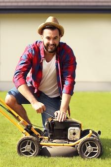 Un jeune homme tond la pelouse