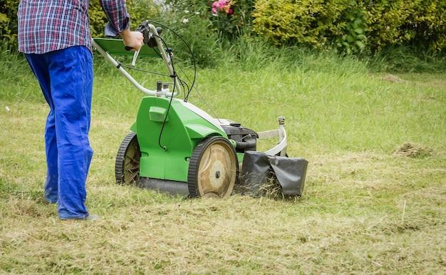 Jeune homme tondant la pelouse avec une tondeuse à gazon