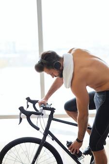 Jeune homme torse nu dans des écouteurs faisant du vélo de papeterie à la maison