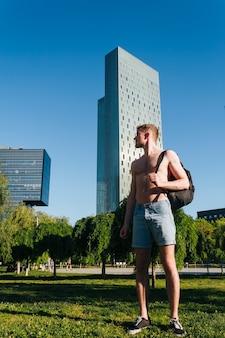 Jeune homme torse nu tenant le sac à dos, debout sur l'herbe dans le parc