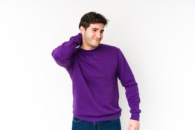 Jeune homme touchant l'arrière de la tête, pensant et faisant un choix.