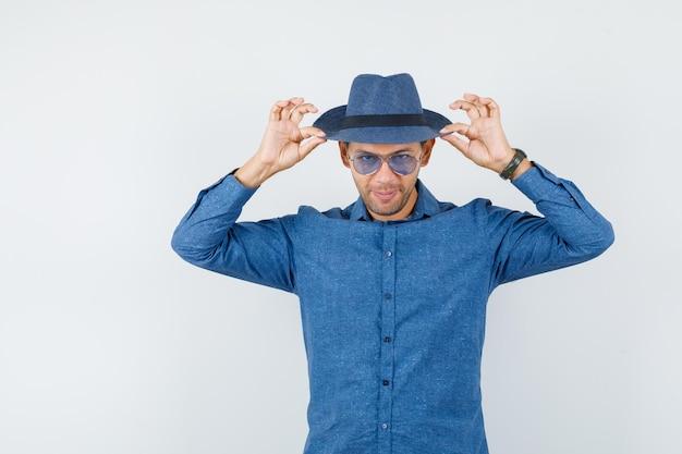 Jeune homme touchant son chapeau en chemise bleue et semblant élégant. vue de face.