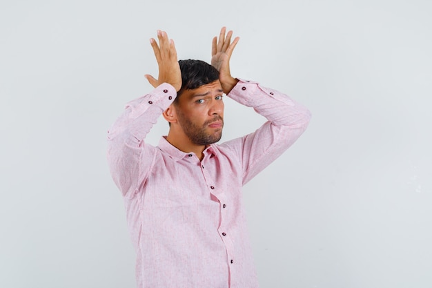 Jeune homme touchant la tête avec les mains en chemise rose et à la fatigue. vue de face.