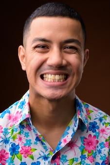 Jeune homme de tourisme asiatique multiethnique sur fond marron