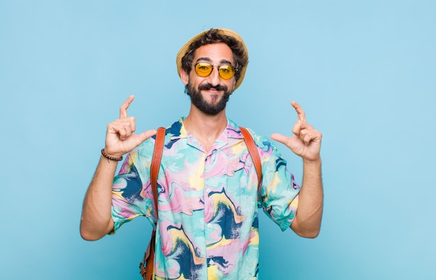 Jeune homme touriste barbu encadrant ou décrivant son propre sourire avec les deux mains, à la recherche de concept de bien-être positif et heureux