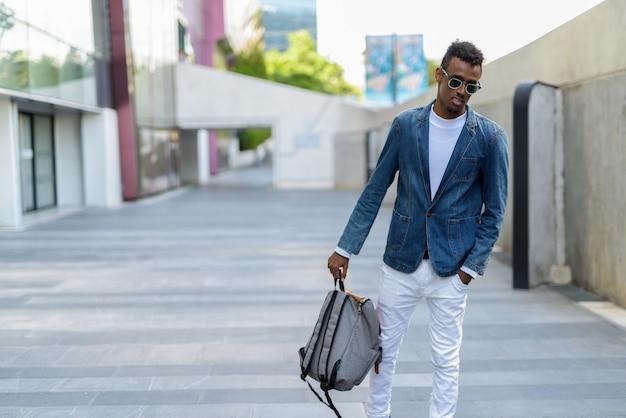 Jeune homme touriste barbu portant une veste en jean et des lunettes de soleil