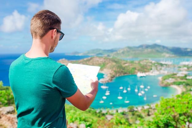 Jeune homme touristique avec une carte du port anglais de shirley heights, antigua, paradis bay sur une île tropicale dans la mer des caraïbes