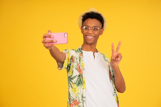 Jeune homme touristique prenant des selfies avec un téléphone portable.