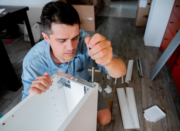 Jeune homme avec un tournevis installer un meuble
