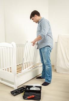 Jeune homme à tout faire assembler un lit bébé blanc dans un nouvel appartement