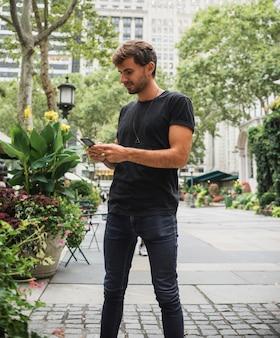 Jeune homme en train de taper au téléphone