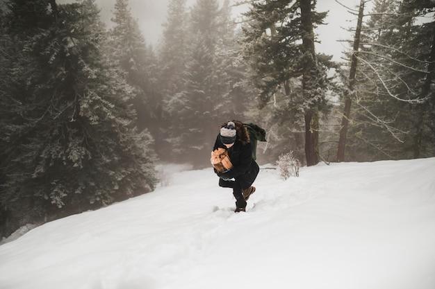 Jeune homme transportant du bois de chauffage en hiver