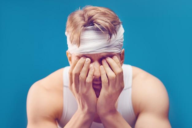 Jeune homme avec un traumatisme crânien dans le bureau des médecins tête bandée avec un pansement