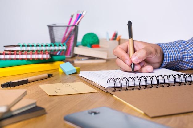 Jeune homme travaillant, apprenant, étudiant à la maison, prenant des notes dans le bloc-notes. étudiant, éducation, rester à la maison, collège, concept universitaire