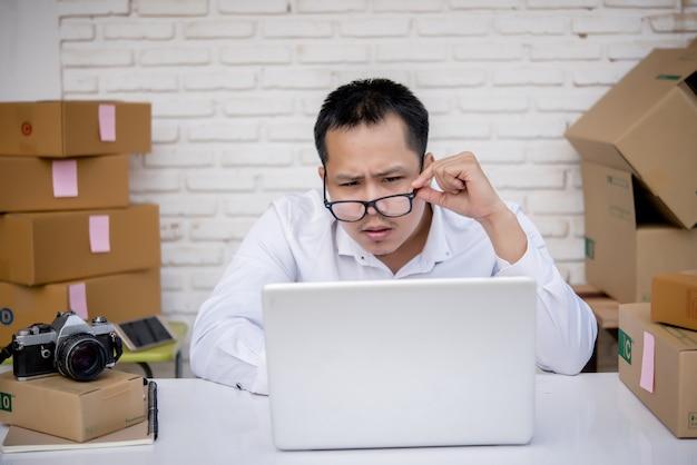 Jeune homme travaillant au marketing en ligne avec ordinateur portable et boîte aux lettres
