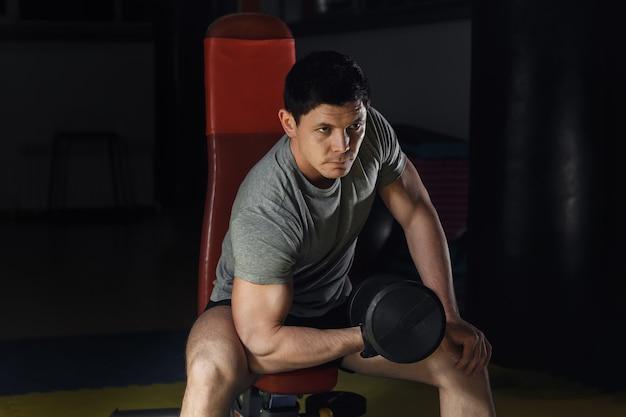 Jeune homme travaillant sur les biceps - boucles de concentration d'haltères.