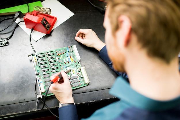 Jeune homme travaillant dans un atelier d'électronique