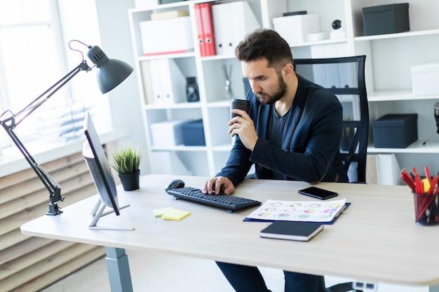 Un jeune homme travaillant dans le bureau à l'ordinateur et tenant un verre de café.
