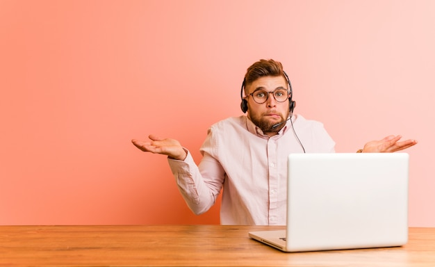 Jeune homme travaillant dans un centre d'appels confus et douteux en le soulevant pour tenir une copie.