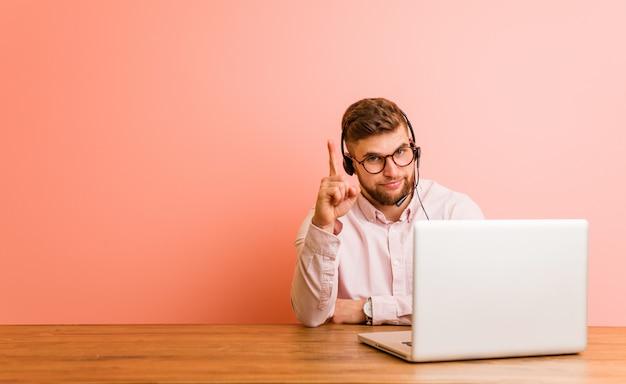 Jeune homme travaillant dans un centre d'appels montrant le numéro un avec le doigt.