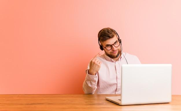 Jeune homme travaillant dans un centre d'appels pointant du doigt vers vous comme si vous vous rapprochez.