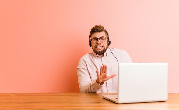 Jeune homme travaillant dans un centre d'appels rejetant une personne montrant un geste de dégoût.