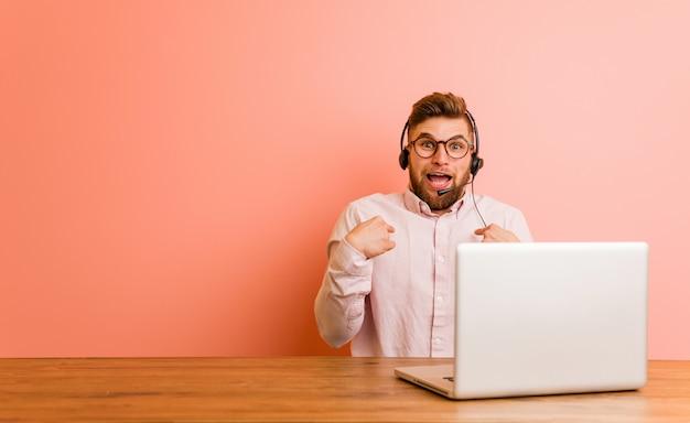 Jeune homme travaillant dans un centre d'appels surpris se montrant du doigt, souriant largement.