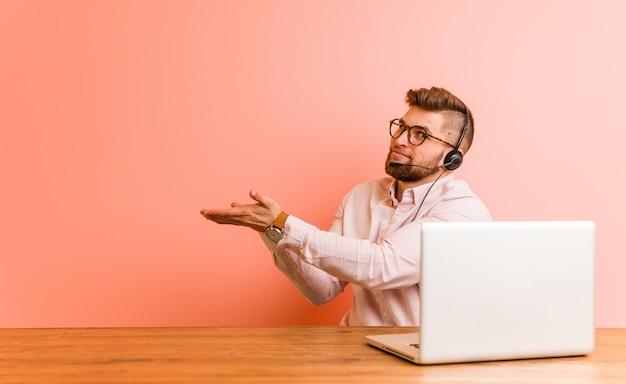 Jeune homme travaillant dans un centre d'appels tenant un espace de copie sur une paume.
