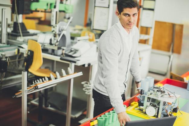 Jeune homme travaillant dans la classe de robotique