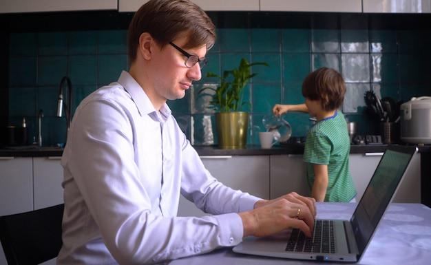 Jeune homme travaillant dans la cuisine à un ordinateur portable avec son fils.