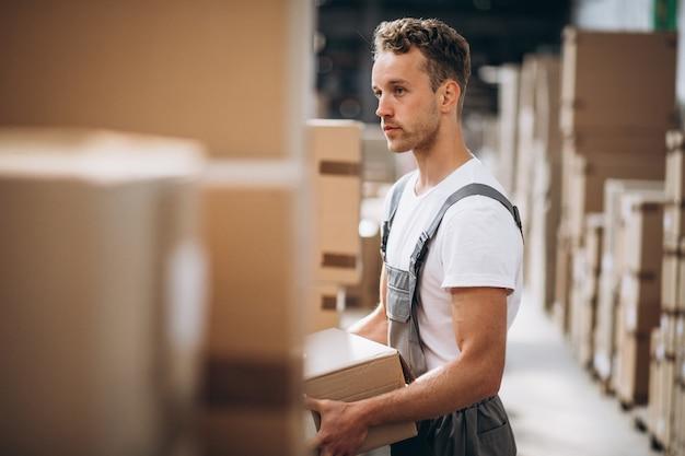 Jeune homme travaillant dans un entrepôt avec des boîtes