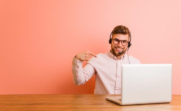 Jeune homme travaillant dans une personne du centre d'appels pointant à la main vers un espace de copie de chemise, fier et confiant