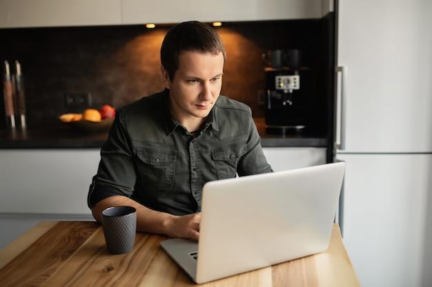 Jeune homme travaillant à domicile. séance, bureau, cuisine, salle, fonctionnement, ordinateur portable, intérieur