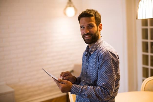 Jeune homme travaillant à domicile sur tablette numérique