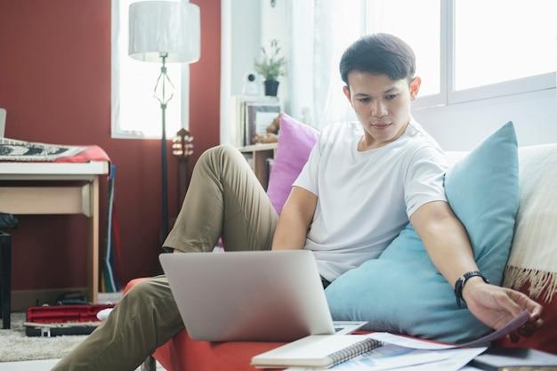 Jeune homme travaillant en ligne et apprenant à la maison.