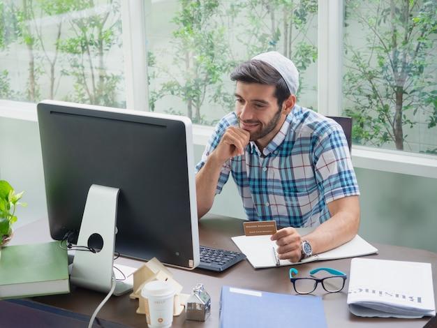 Jeune homme travaillant à la maison avec une carte d'assurance maladie